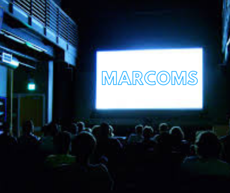 Darkened cinema the word Marcoms is on the screen